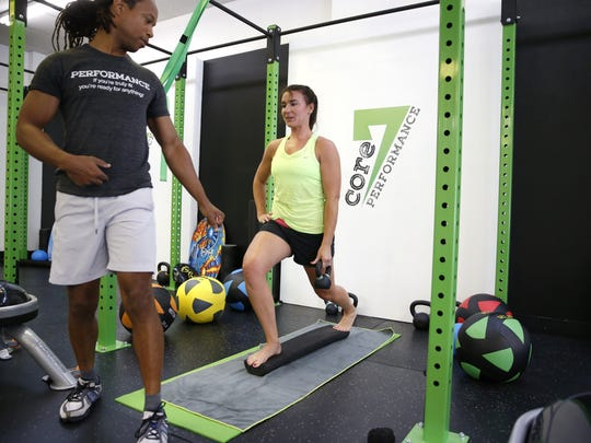 Sherman Rosier, creator of the Core 7 Performance workout, instructs Erin Wilder at his gym.