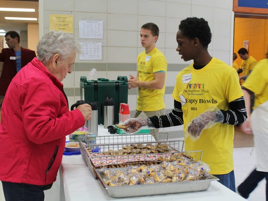 A volunteer hands a woman a cookie at Saturday's Empty