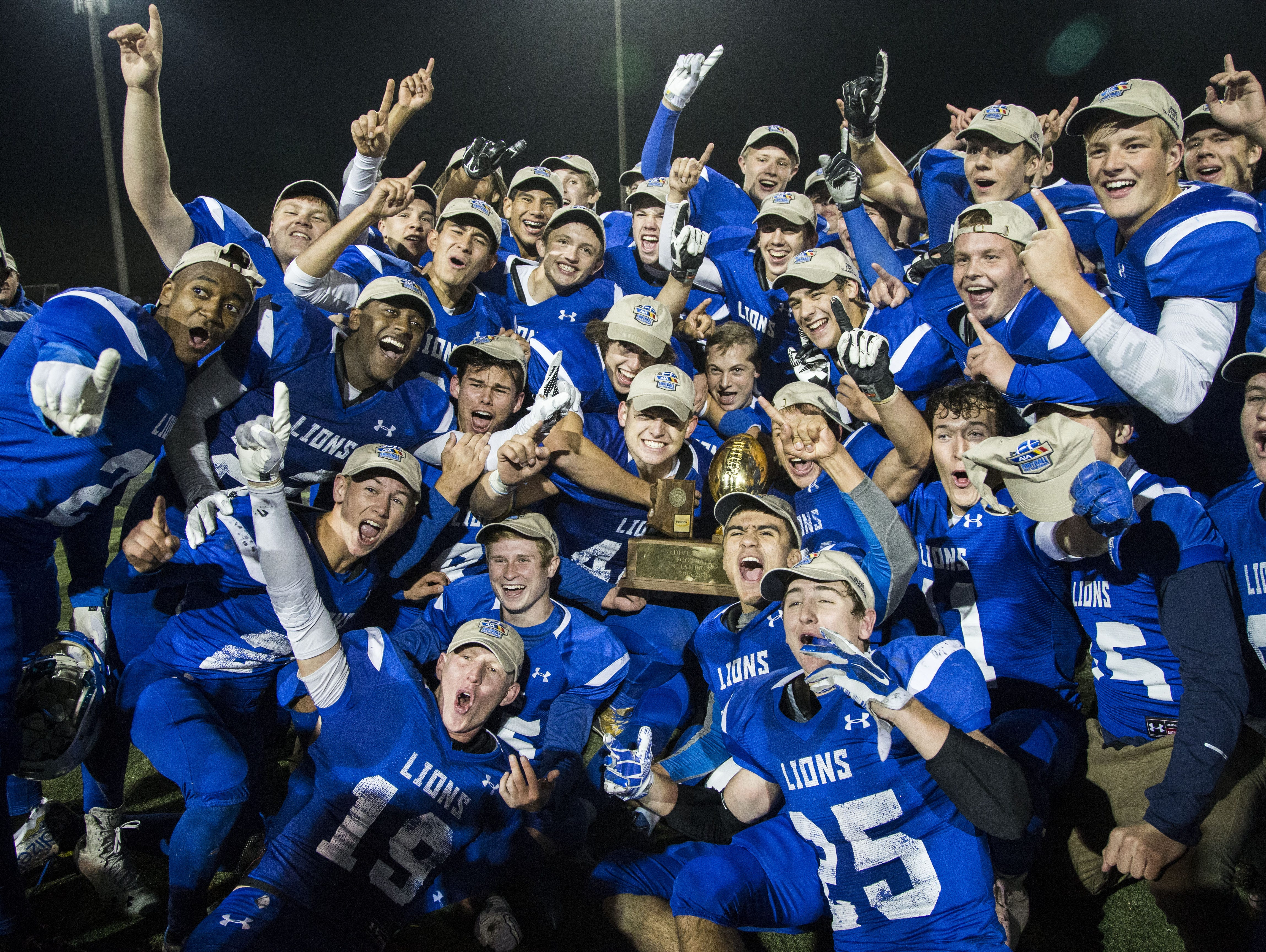 Pusch Ridge celebrates with the trophy after beating Northwest Christian for the Division IV State Championship at Chaparral High School on Nov. 28, 2015 in Scottsdale Ariz.