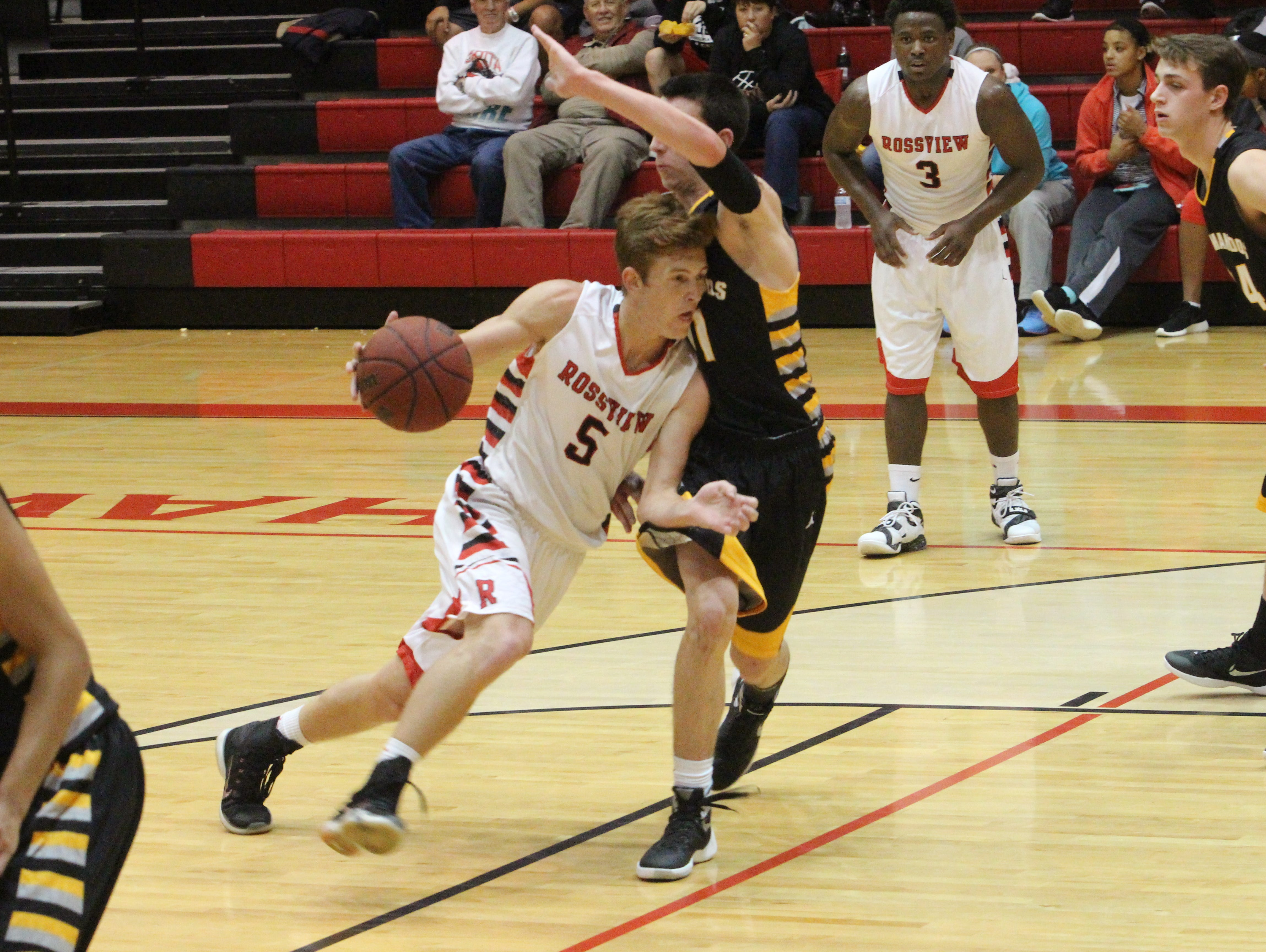 Rossview's Cannon Campbell (5) drives past a Hendersonville defender during the first half of their boys' basketball game Monday at Rossview High School.
