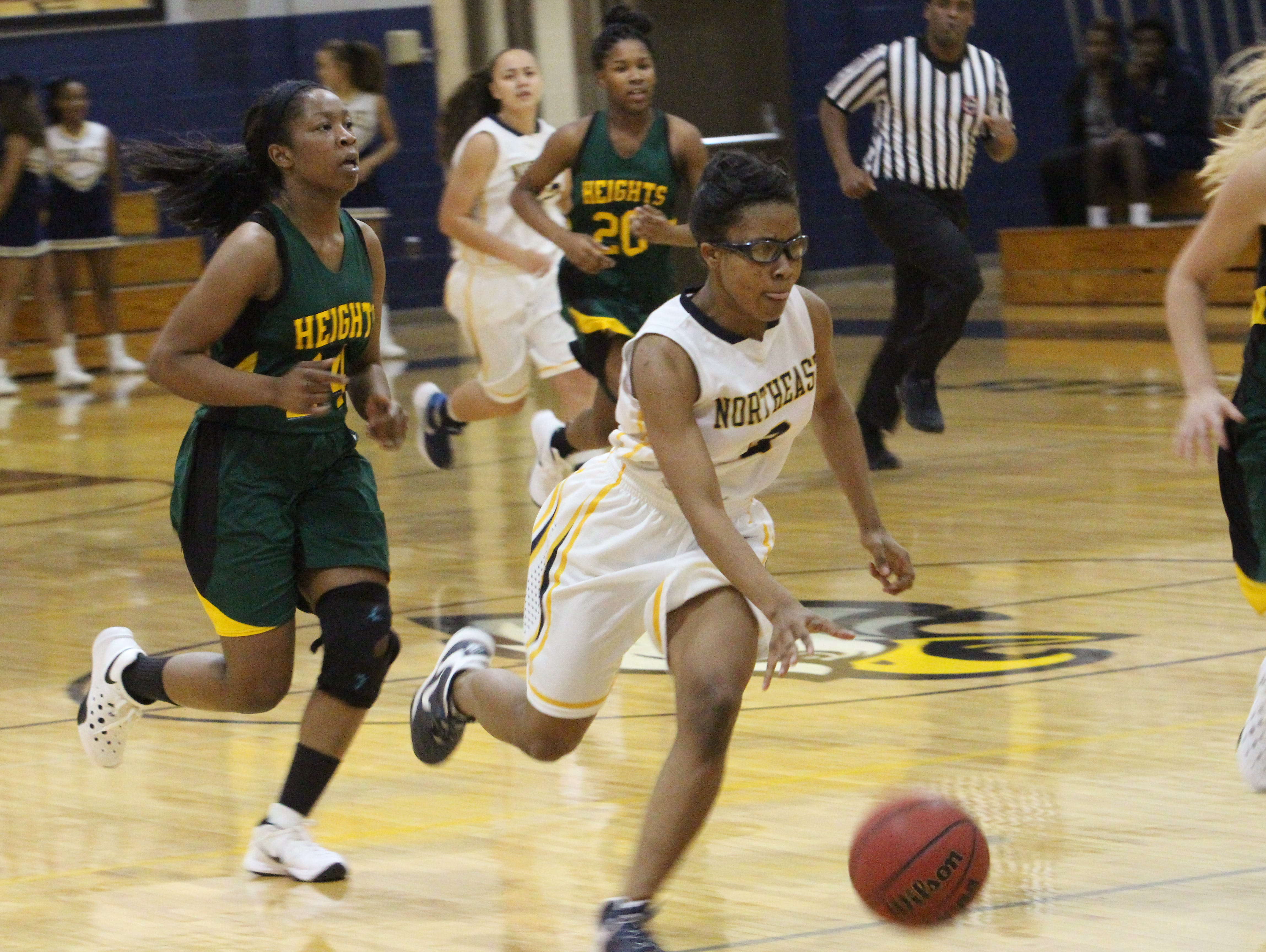Northeast's Essence Brown dribbles down the court on a fastbreak during the first quarter of their game against University Heights Academy (Ky.) Thursday night at Northeast High School.