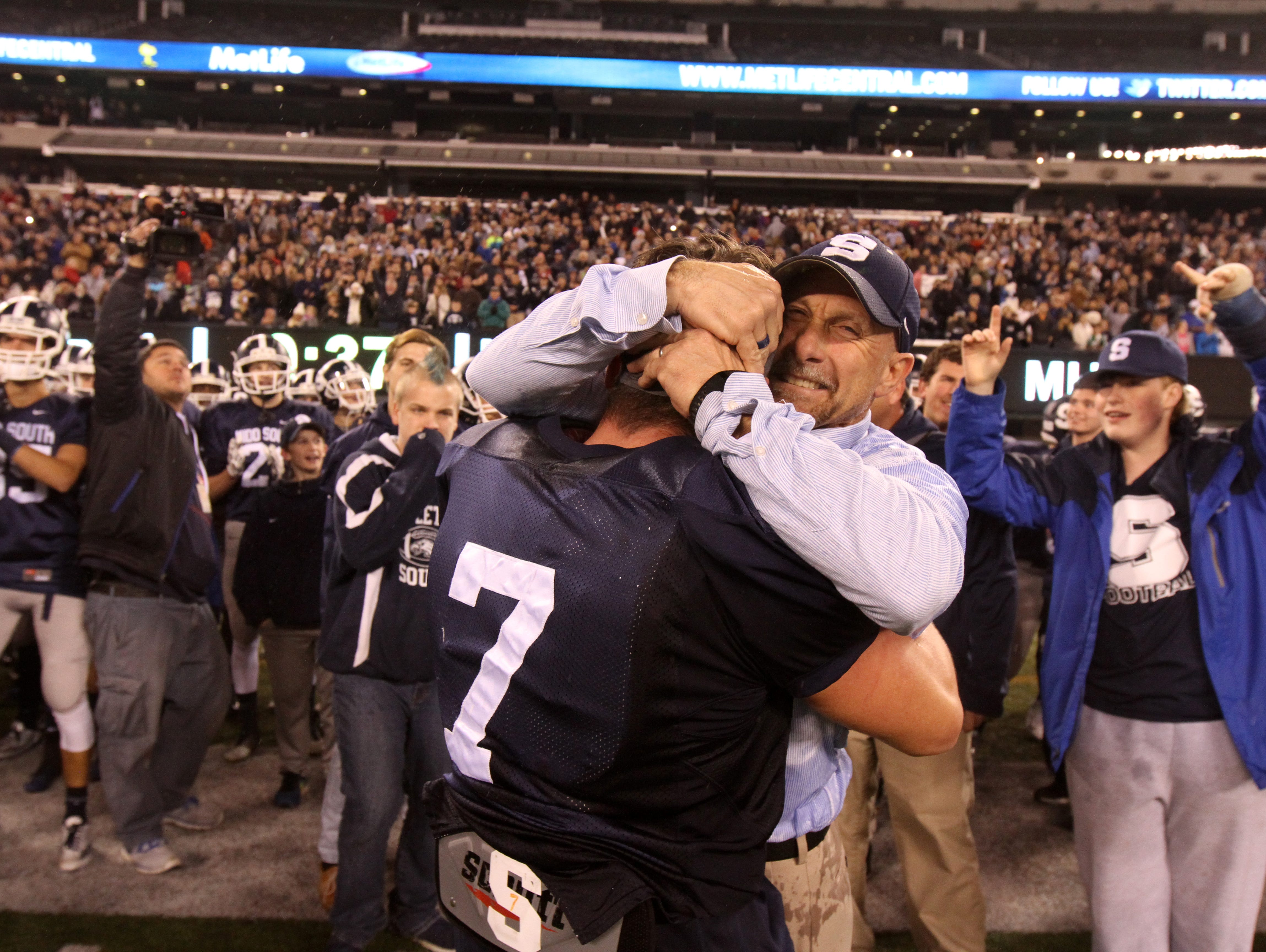 Middletown South High School head coach Steve Antonucci hugs #7 Robert Hulse after winning the state title against Phillipsburg in the North 2 Group IV game of the 2015 NJSIAA/MetLife Stadium High School Football Championships at MetLife Stadium in East Rutherford, NJ Saturday December 5, 2015.