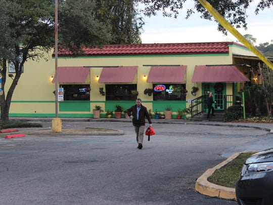 A Tallahassee Police Department forensic investigator exits El Patron where two people were killed and two were injured in a shooting Wednesday Dec. 9.