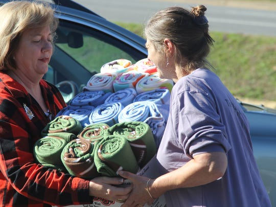 Mary Fran Strickland, left, hands Tallahassee Democrat Community Content Editor Martha Gruender more than a dozen blankets Saturday.