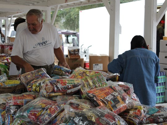 Customers look through large and small snack bags at the booth Sunday at the T & W Flea Market.