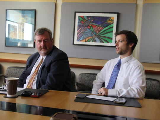 Department of Public Instruction spokesman Tom McCarthy, right, and John Johnson, left, the agency's director of education information services, note in a meeting with Tony Evers and Wisconsin Center for Investigative Journalism reporters that five- and six-year graduation rates in Wisconsin have improved in recent years, although a racial gap remains.