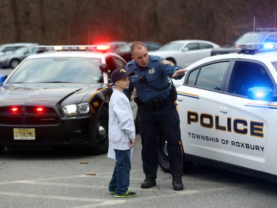 Ptl. Sean Gaffey instructs 8-year-old James DeChristofano of Roxbury on how to approach a stopped vehicle. James and his brother won a chance to ride with Roxbury police and pulling over two Detectives, issuing them a warning for not wearing a seatbelt. December 16, 2015, Roxbury, NJ.