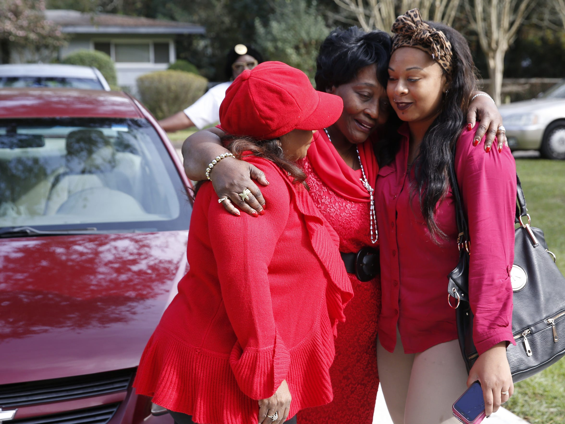Corine Beard, center, hugs her daughter Yvette Derice, left, and grandaughter Markeshia Browning Friday in the driveway of Corine's new home, the first she has ever owned.