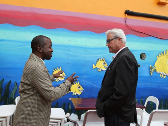 Morristown Mayor Timothy Dougherty talks to artist Ronald Ritzie who painted the mural for Monster Sushi in Morristown on September 28, 2015. Alexandra Pais / For The Daily Record