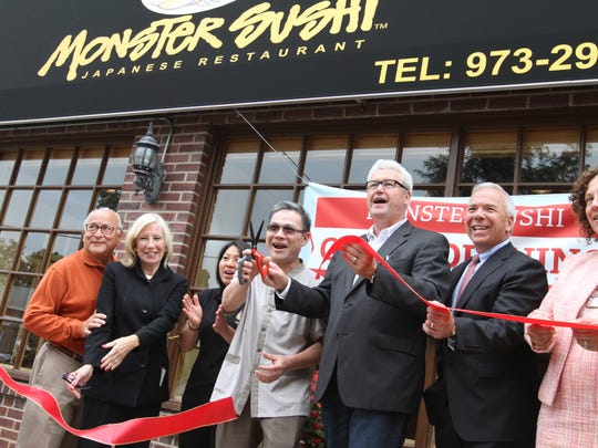 From left to right; Steve and Susanne Newmark, building owners, Nhu Le and On Le, of Monster Sushi, Mayor Timothy Dougherty, President of Morris County Chamber of Commerce, Paul Boudreau, and Councilwoman Alison Deeb cut the ribbon during the Grand Opening of Monster Sushi in Morristown on September 28, 2015. Alexandra Pais / For The Daily Record