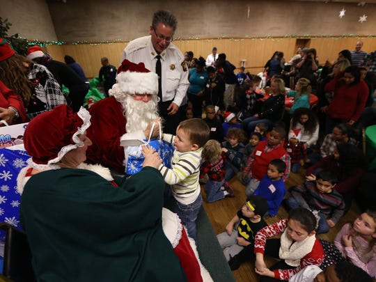 Marilyn and Daniel Schievella of Leonia as Santa and Mrs. Claus with their son Undersheriff for the Morris County Sheriff's Office William Schievella, give out gift bags at the Italian American Police Society of New Jersey's annual Big Brothers and Sisters of New Jersey Children's Christmas Party at  the Whippany American Legion Hall. December 19, 2015, Whippany, NJ.