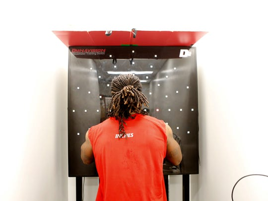 Silverberry Mouhon, University of Cincinnati senior and defensive lineman,  participates in an exercise to train his peripheral vision at UC Wednesday, December 16, 2015. Mouhon has had zero concussions during his college football career.  UC's sports medicine department started the training five years ago to prevent concussions in their athletes. Athletes are able to widen their peripheral vision by a few degrees, which helps them anticipate being hit.