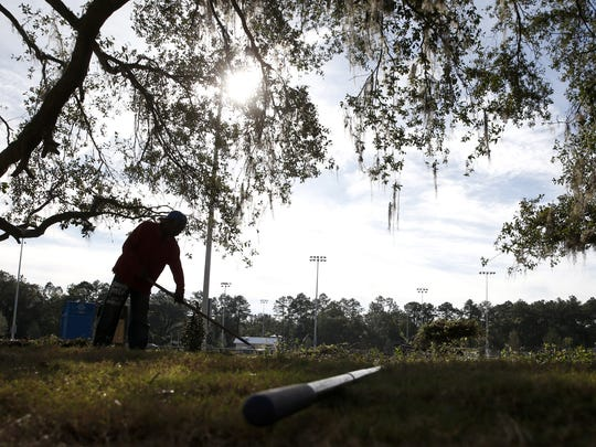 A landscaper grooms a tree on the edge of the new, 170-acre Fred George Greenway and Park, set to open to the public on Feb. 17.
