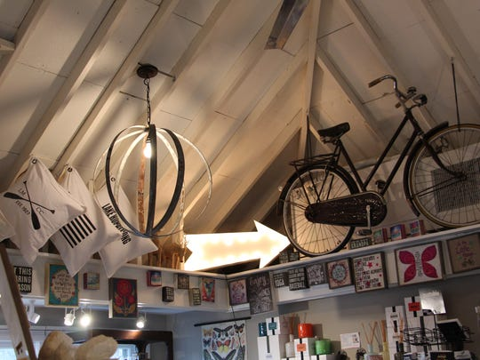 An assortment of eclectic gifts on display at Shelter Vintage shop in Sparta include a hanging light fixture made from the metal belts on wine barrels, a vintage bicycle, quirky signs and personalized pillows.