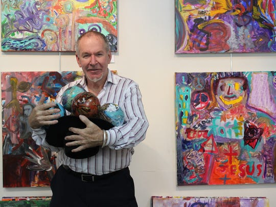 Artist Robert Miley holds a few of the ornaments that