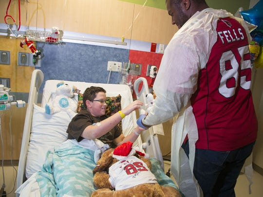 "Tight end Darren Fells of The Arizona Cardinals Football Club's talks to patient Ryder Ruiz, 13 during the annual ""Teddy Bear Express"" visit at Phoenix Children's Hospital on Dec. 22, 2015."