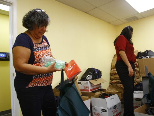 Administrative service officer Dinah Lewis, left, and spokeswoman Delilah Goodluck go through donation items Dec. 10 at the Navajo Nation Department for Self Reliance office in Farmington.