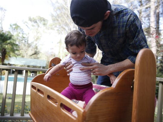 Richie Sanchez, helps his daughter, one-year-old Aria Luz Sanchez, into the cradle they used for her in her first six months. The cradle was hand furnished by Bob Bruggner for his own children and has ventured throughout the U.S. with family members, neighbors and friends to be used by over 30 different families along the way.