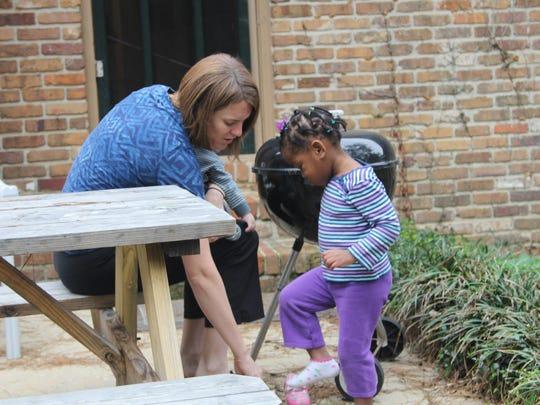 Calyn Stringer helps Maya, 2, put her shoe on while holding infant Banjamin.