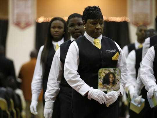 Members of the Reed and Hall Mortuary staff carry a photo of Barbara Dawson during her funeral at the Liberty County High School Gymnasium in Bristol on Saturday.