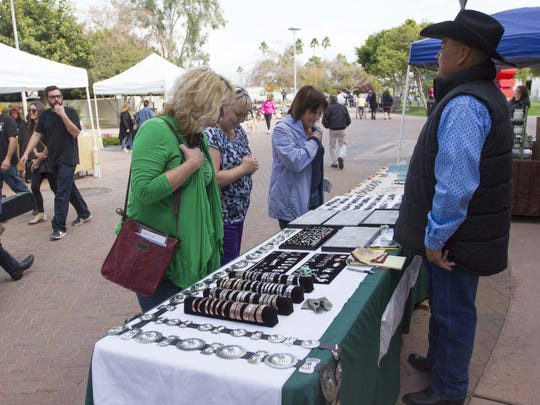 Ladies take a look at jewelry from vendors during the