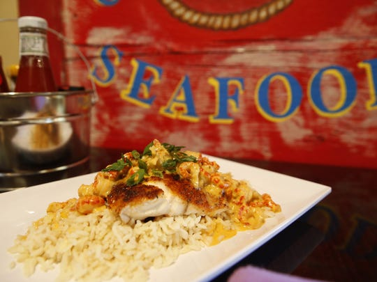 Fresh catch blackened Grouper over shrimp and rice with a smoked cheddar crawfish topping, on the menu at Wahoo Seafood Grill.