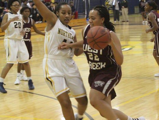 West Creek's Kiaja McCabe (22) tries to dribble around