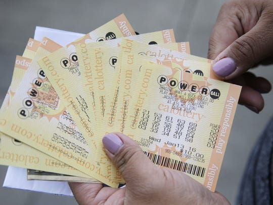 A person shows Powerball tickets she bought on Tuesday,