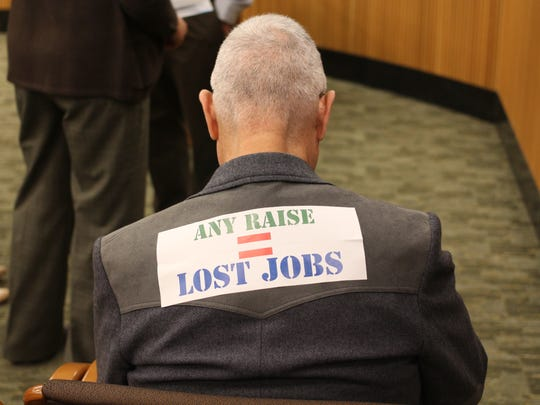 "An audience member at a public hearing on raising the minimum wage wears a sticker on his back that reads ""Any raise = lost jobs."""
