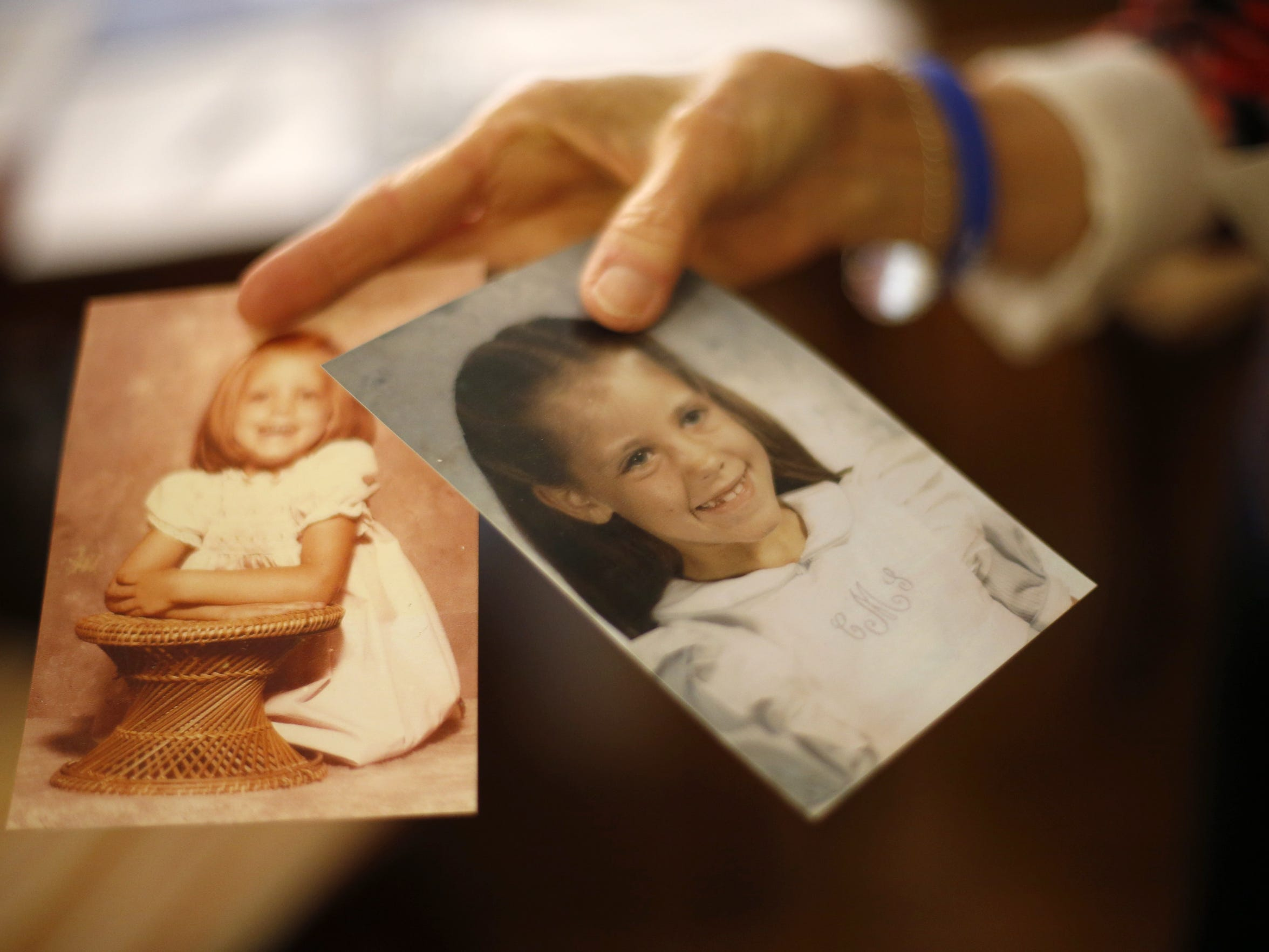 Karen McGehee holds old photos of her daughter Caroline at her home in Tallahassee.