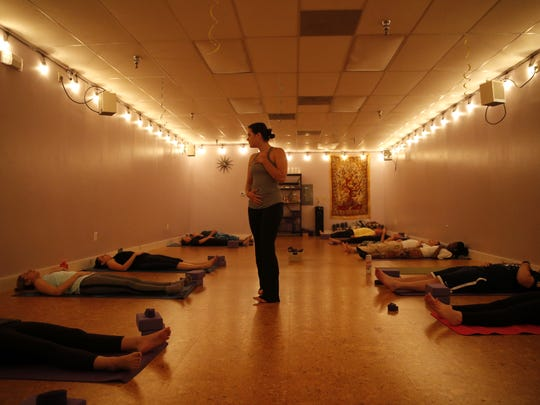 Journey's in Yoga Instructor Rachel Spells eases students into the beginner's class with breathing excersizes on Thursday evening at their Tallahassee studio.