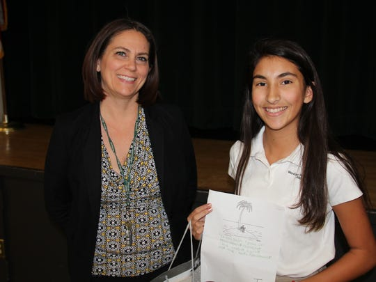 Cartoon Caption Winner. Camila Martinez of Scotch Plains receiving a writer's goodie bag from Dr. Corinna Crafton