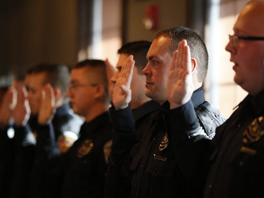 Richard Parnell and the rest of the 12 graduating Southport Police Academy reserve officers are sworn in during their graduation, held at Scotty's Brewhouse on Jan. 18, 2016.