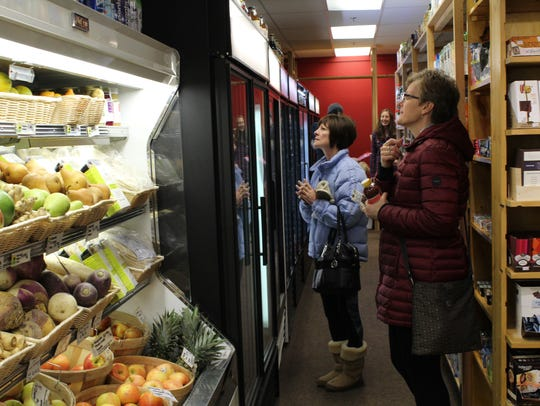 Customers look at refrigerated items at Downtown Grocery's