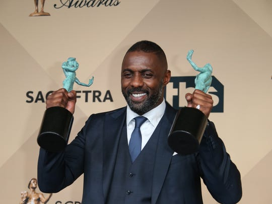 Idris Elba holds up his awards for Outstanding Performance