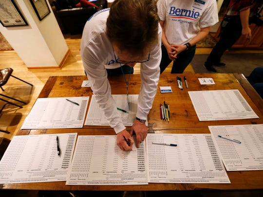Pete Malmberg, a Bernie Sanders precinct captain, signs in Feb. 1, 2016, at a home caucus site in Rippey, Iowa.