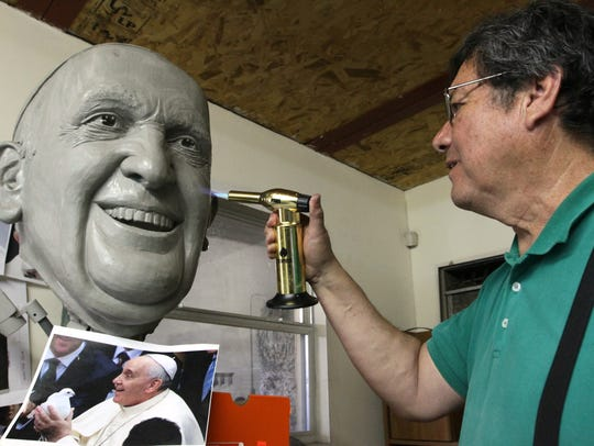 Sculptor Pedro Francisco Rodríguez works on the head