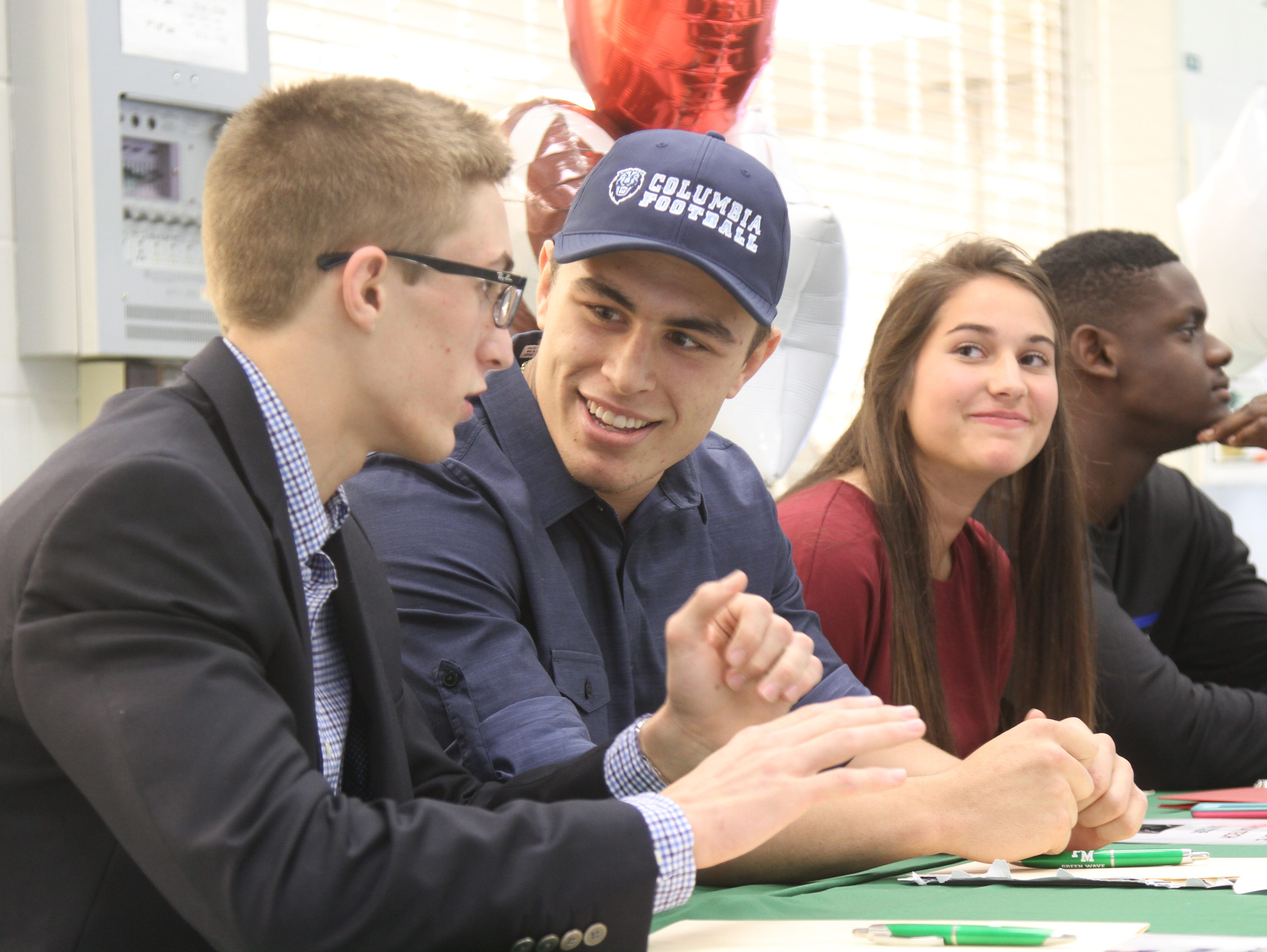 Colton Thomas, left, Levi McQuinn, Emily Swope, and Amos Corgelas, of Fort Myers High School prepare to sign their letters of intent during National Signing Day on Wednesday.