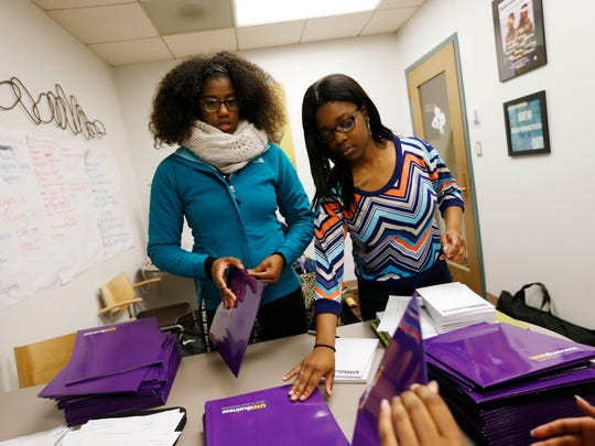 Junior Brianne Baylor (left) and freshman Alexis Tellis help sophomore Melanie Majeed assemble packets December 10, 2015, in the office of diversity coordinator Jonathan Cox at the University of Northern Iowa in Cedar Falls.