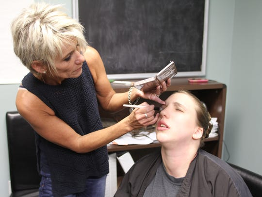 Sam Suchanek, 23, sits patiently as make up is applied