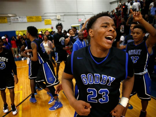 Godby's Montre Edwards celebrates with his teammates after their 49-47 Region 1-5A semifinal game win against Rickards Tuesday.