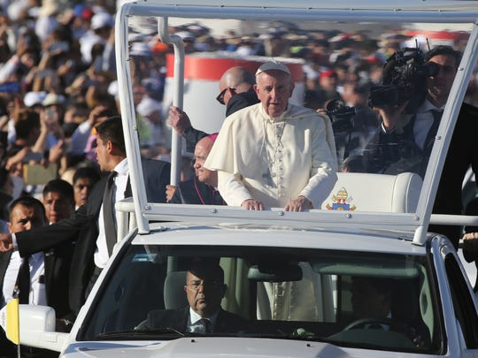 Pope Francis rides in his popemobile Wednesday before placing flowers at three crosses at an altar close to the Rio Grande, where he then turned and blessed a group on the United States side of the Rio Grande.