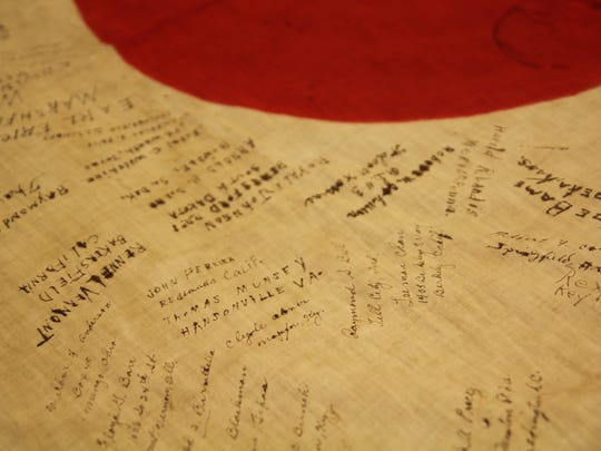 The signatures of 189 American soldiers appear on a WWII Japanese flag.