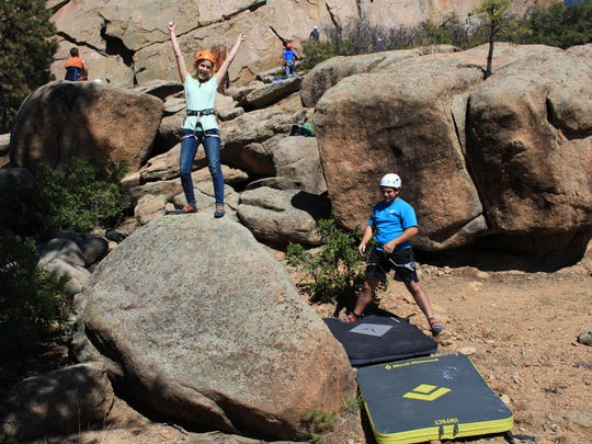Liza Elsbury and a spotter pose for a photo after bouldering at Tres Piedra outside Taos in November.