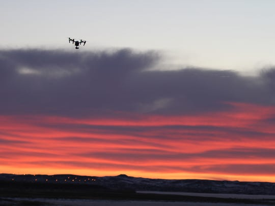 A drone flies toward sunrise at Fort Peck Dam.