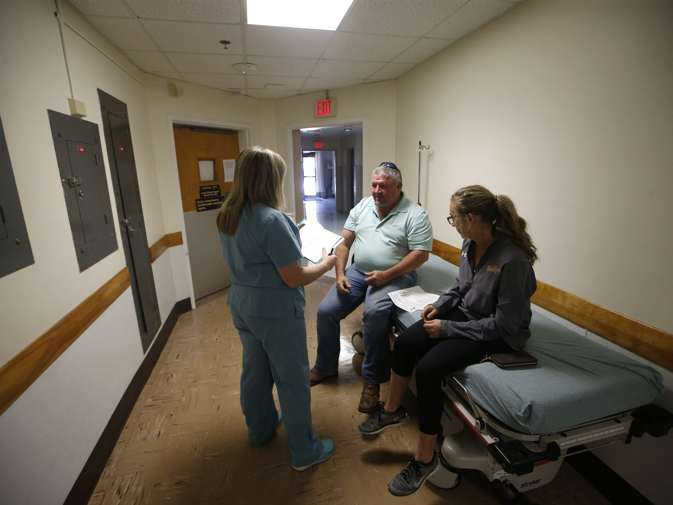 Hanna Bailey, 16, and her father Andy talk to Licensed Practical Nurse Delynda Bailey, who is related by marriage to the family, about Hanna's knee injury to see if she can be cleared to play softball later that afternoon on Friday, Feb. 19, 2016. The phrase of 'there are no strangers in this town' was a common one inside the hospital walls.