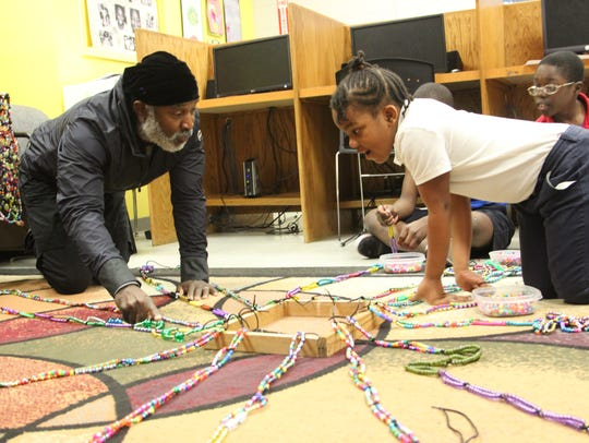 Nick Cave shows children how to make beaded blankets