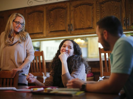 Tessa Miller, 17, laughs with family teachers Jaclyn