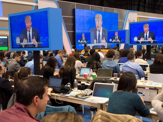 Members of the media view Donald Trump on screen at