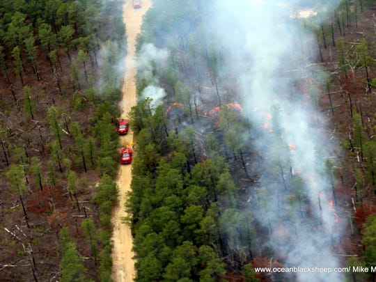 Pilots photographed a brush fire over Barnegat on Sunday. Two brush fire trucks are seen on a dirt road in the Pine Barrens.